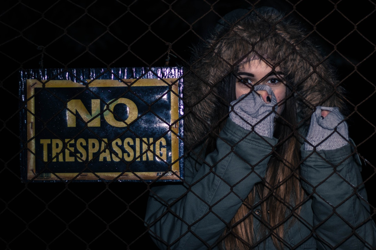 woman standing next to a no trespassing sign